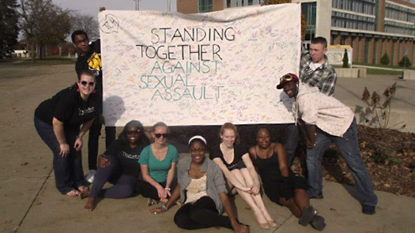Photo of peer educators holding large sign that says 'Standing together against sexual assault.'