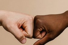 A white hand and a black hand fist bumping.