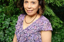 Dr. Irma Lopez standing in front of foliage.