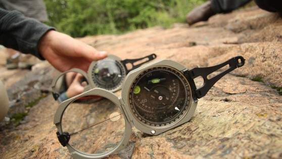 Geologist using a compass on a rock.