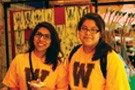 """Two students wearing yellow shirts with brown """"W"""" logo smiling and posing for a photo."""