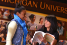 Two WMU students smiling at each other. One student is holding an opened book.