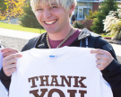 "Man holding ""Thank You"" shirt"