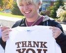 "Man holding ""Thank You"" shirt"