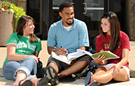 Students sitting outside reading.