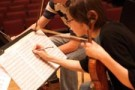 Female violinist writing notes on her music.