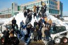 Landscape employees on mound of snow.